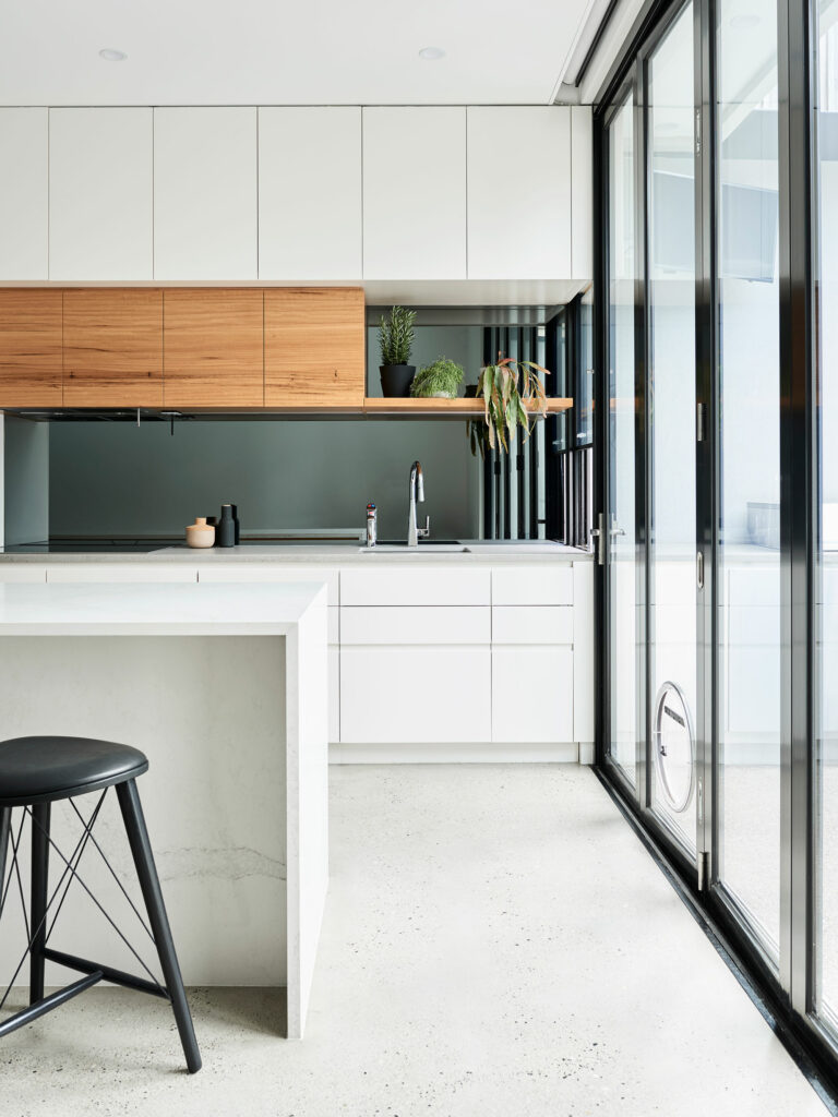 Maike Design white kitchen with concrete floor and white marble bench