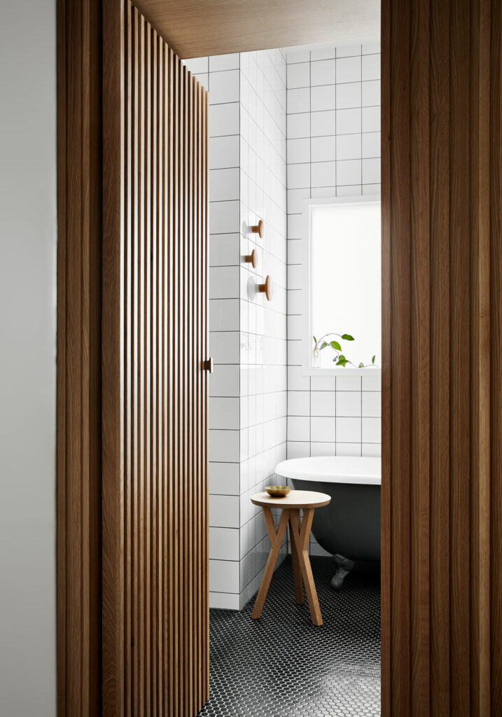 Maike Design bathroom with clawfoot bath and concealed timber door