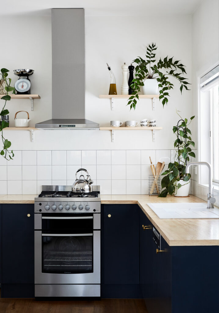Maike Design navy blue kitchen with brass hardware and open kitchen shelving