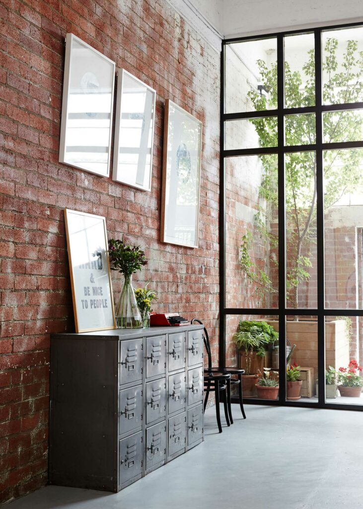 Maike Design Creative workspace, warehouse conversion. Redbrick wall, industrial lockers and indoor tree