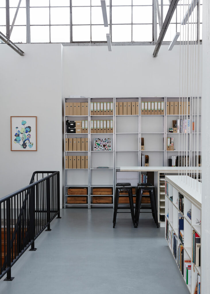 Maike Design Creative workspace, warehouse conversion. Steel book shelves and office space