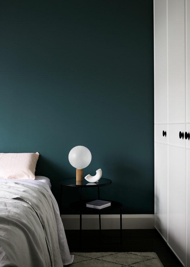 Maike Design dark teal bedroom with custom wardrobe door detail. Linen sheets and artwork.