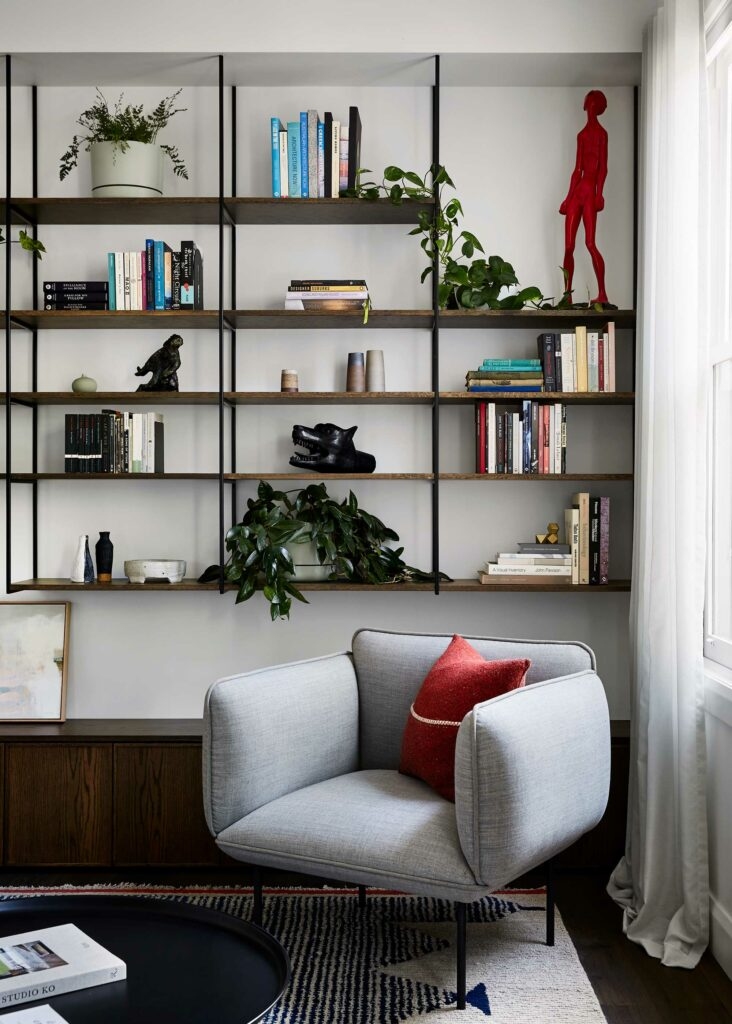 Maike Design lounge. Open bookshelves with black steel frame, decor and plants. Grey armchair and textured woolen rug.