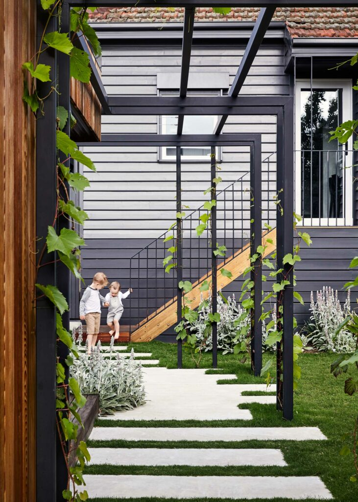 Maike Design backyard. Charcoal painted weatherboard and cedar cladding. Black painted pergola and grape vines. Concrete pavers in lawn
