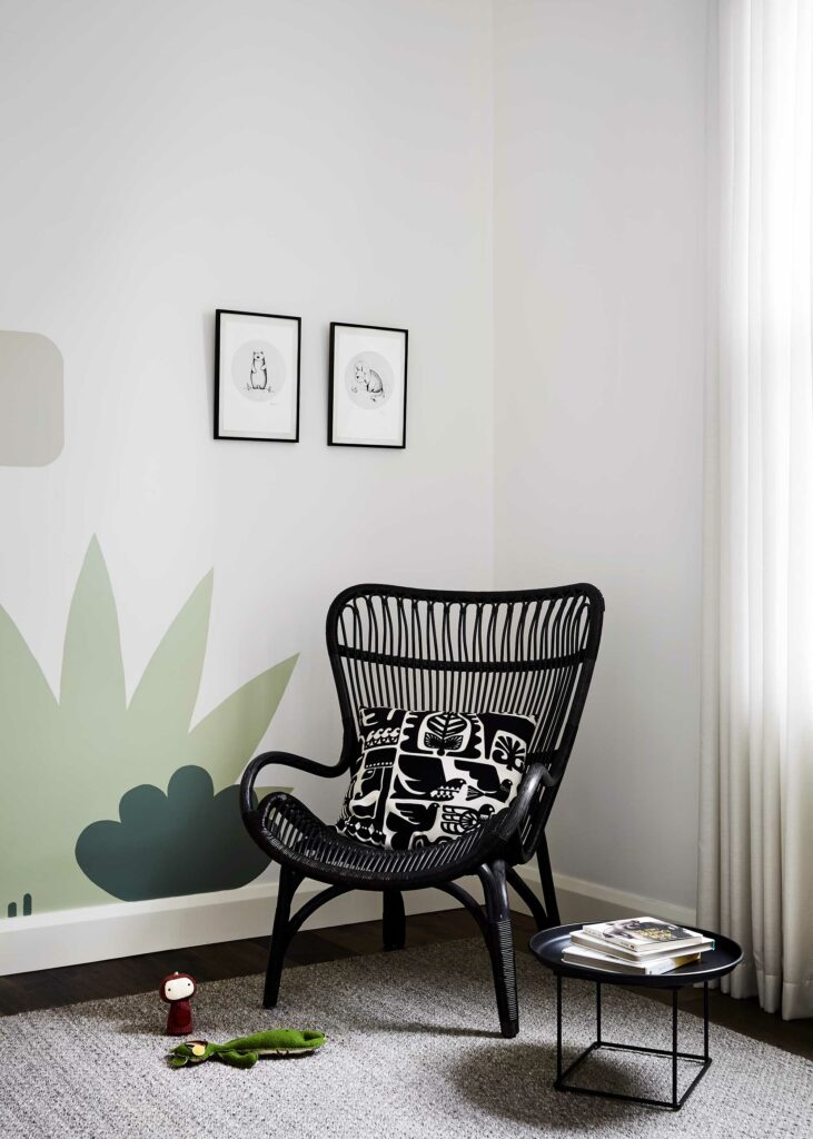 Maike Design nursery with artwork, wicker chair and hand painted mural