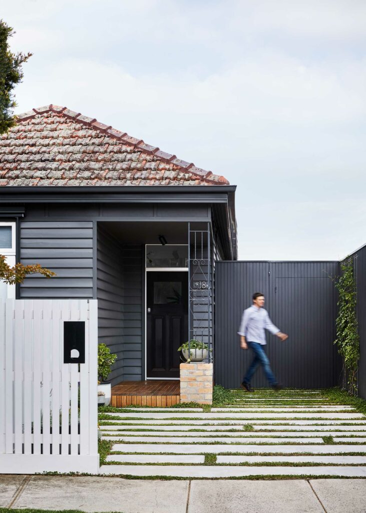 Maike Design weatherboard exterior painted charcoal. Concrete path with planting.