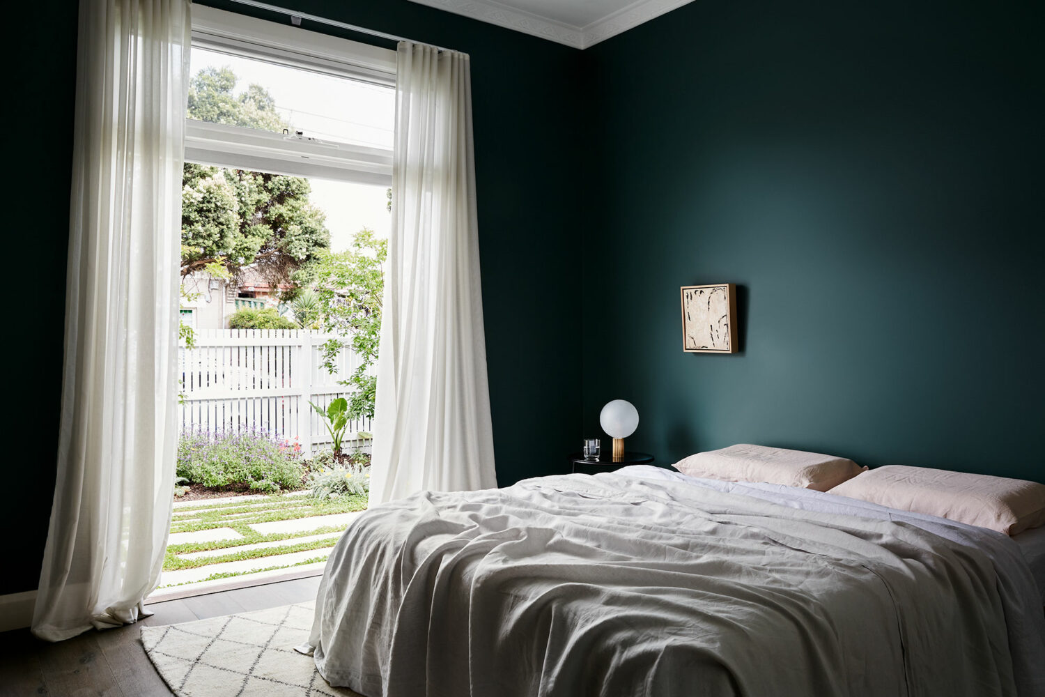 Maike Design dark teal bedroom opening onto private courtyard. Linen sheets and artwork.