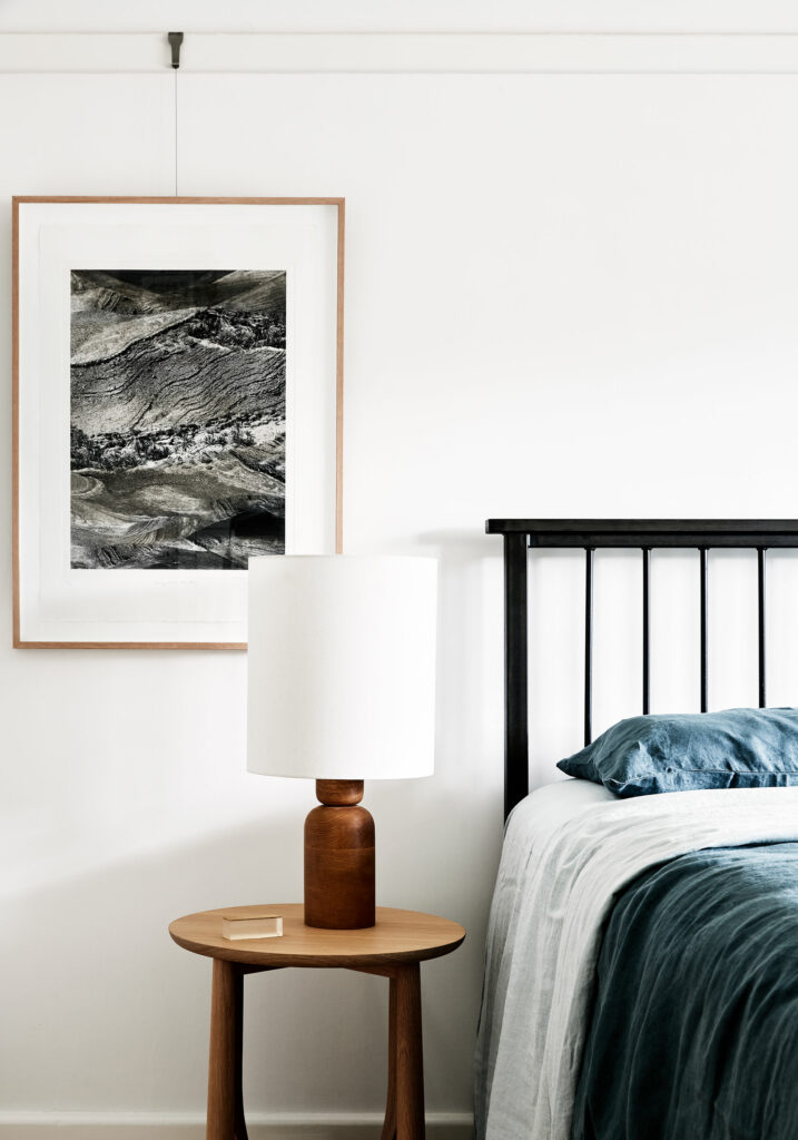 Maike Design Bedroom. Timber lamp and side table. Photographic artwork. Blue linen.