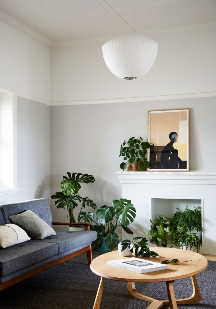 Maike Design renovated Californian Bungalow. Living room with indoor plants, fireplace and artwork