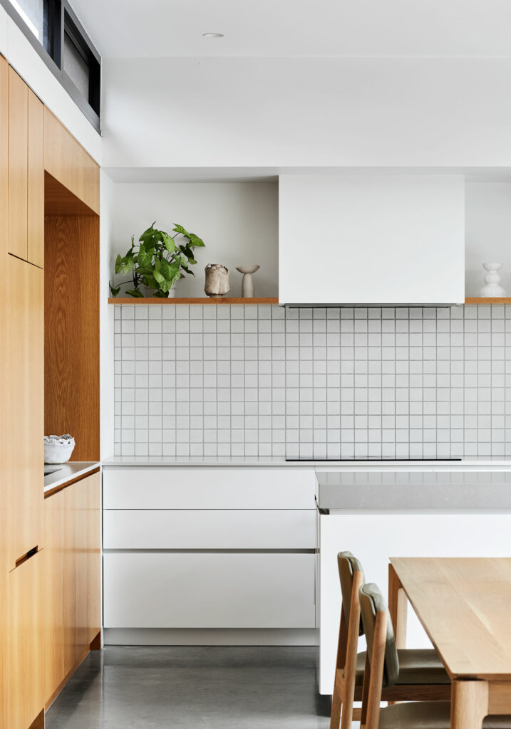 Maike Design kitchen. Timber joinery, white joinery with stone tops. Textured tile splashback. Timber dining table