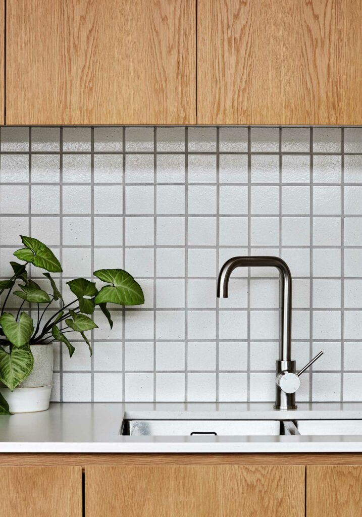 Maike Design kitchen. Timber joinery with stone tops. Textured tile splashback.