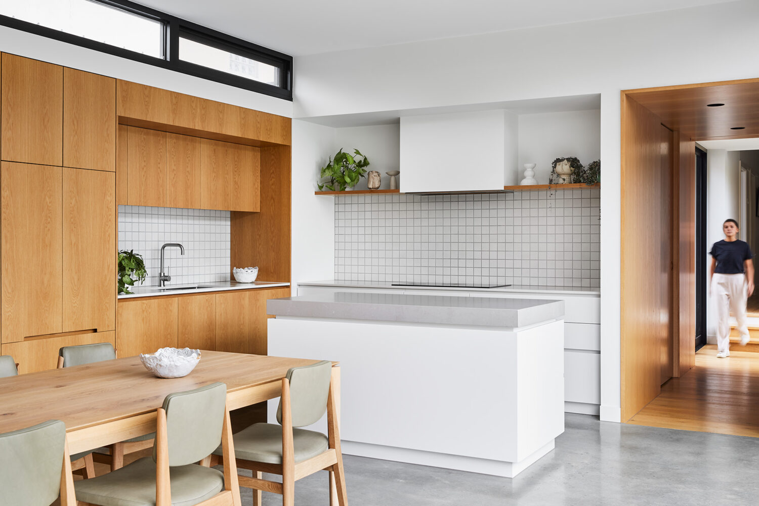 Maike Design kitchen. Timber joinery, white joinery with stone tops. Textured tile splashback. Timber and glass hallway link