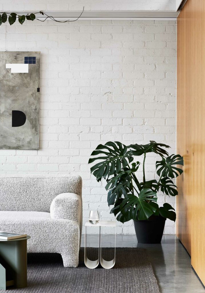 Maike Design lounge room. White painted bricks, indoor plants and timber joinery
