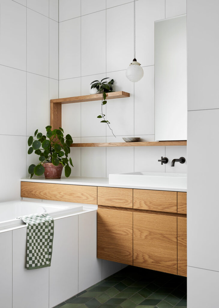 Maike Design bathroom. White and green tiles. Antique pendant light, timber joinery and charcoal tapware