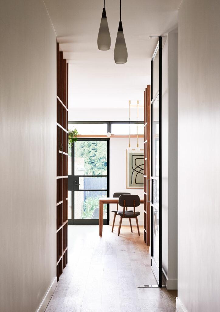 Maike Design lounge room. Vintage lights, hallway, timber floors timber joinery