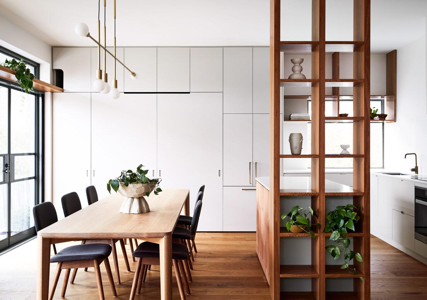 Maike Design kitchen and dining room. Open timber shelves, indoor plants, brass pendant light, teracotta tiles, timber floors.