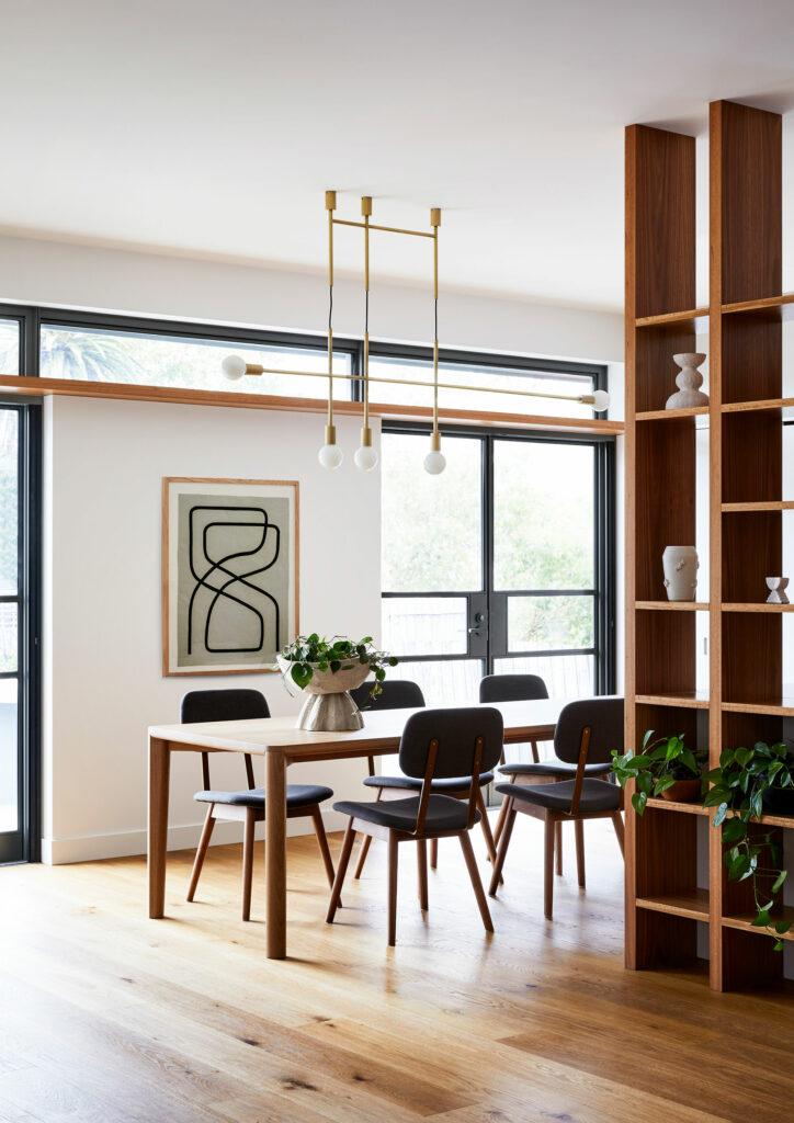 Maike Design dining room. Open timber shelves, brass pendant light. Minimal artwork. Indoor plants. Steel windows