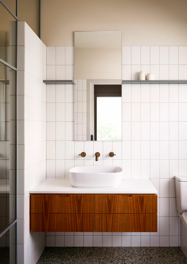 Maike Design bathroom. White tiles, timber joinery and brass tapware. Peach painted ceiling. Terazzo tiles