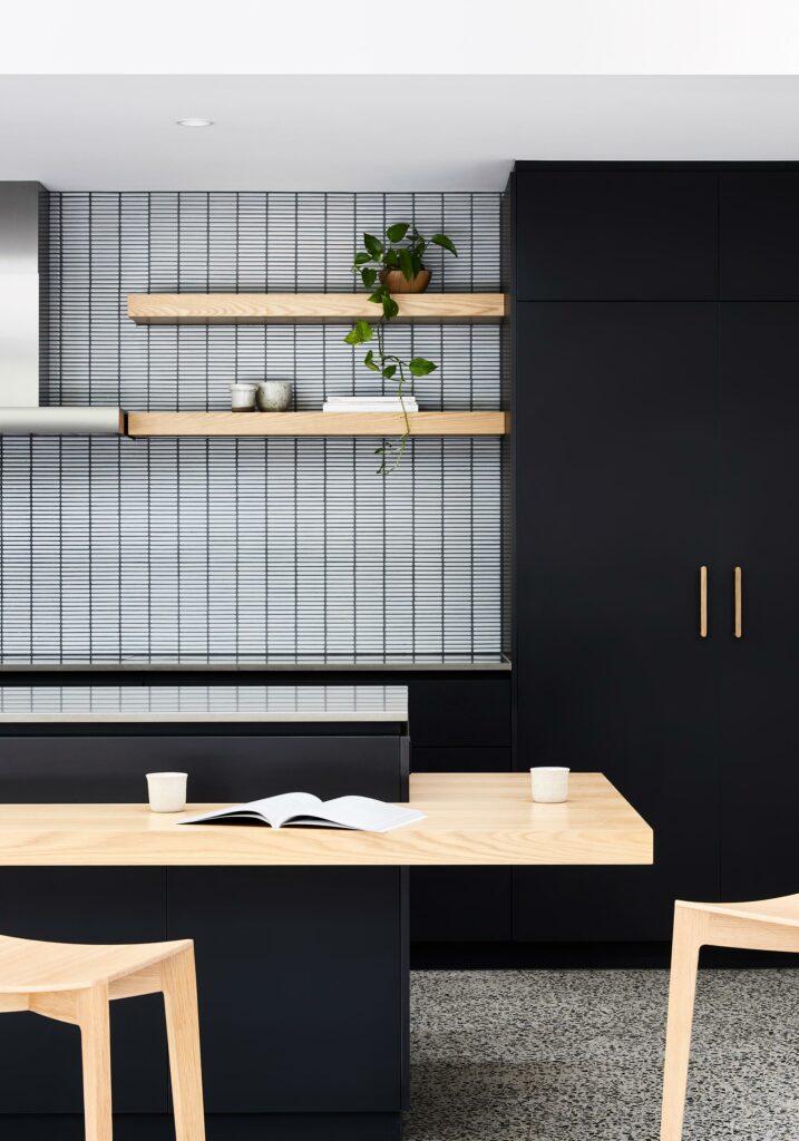 Maike Design Black kitchen. Tiled splashback and timber shelves.
