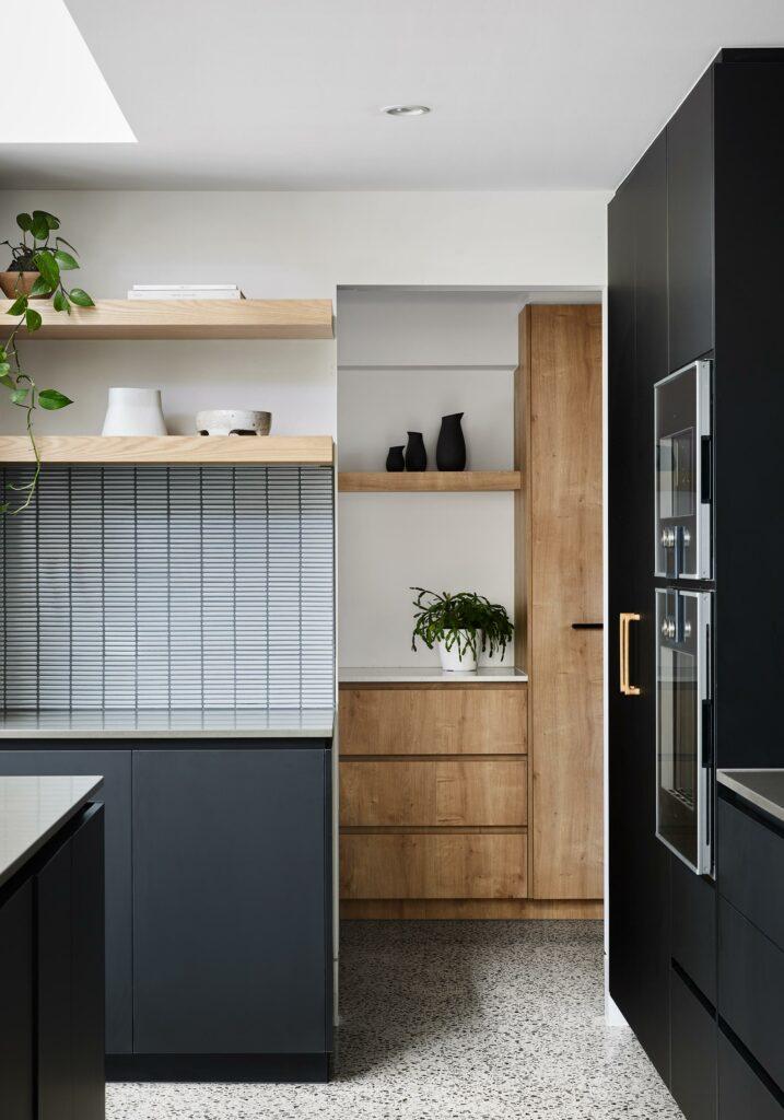 Maike Design Black kitchen and timber butler's pantry. Tiled splashback and timber shelves.