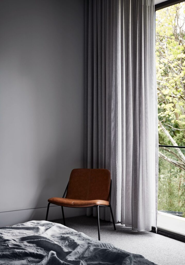 Maike Design bedroom. Sheer curtain and large window. Leather chair
