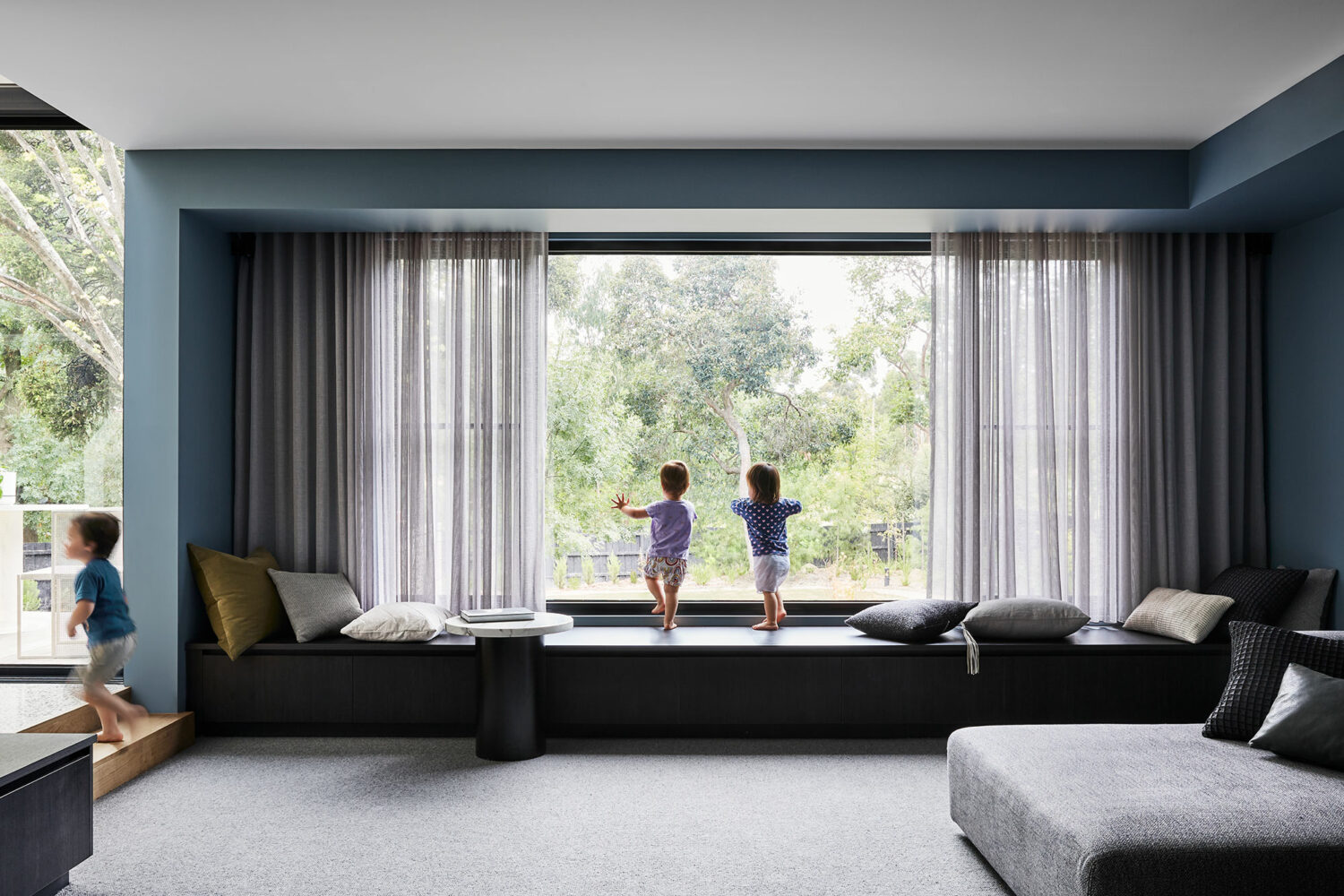 Maike Design lounge room. Bench steat and sheer curtains. Blue painted walls