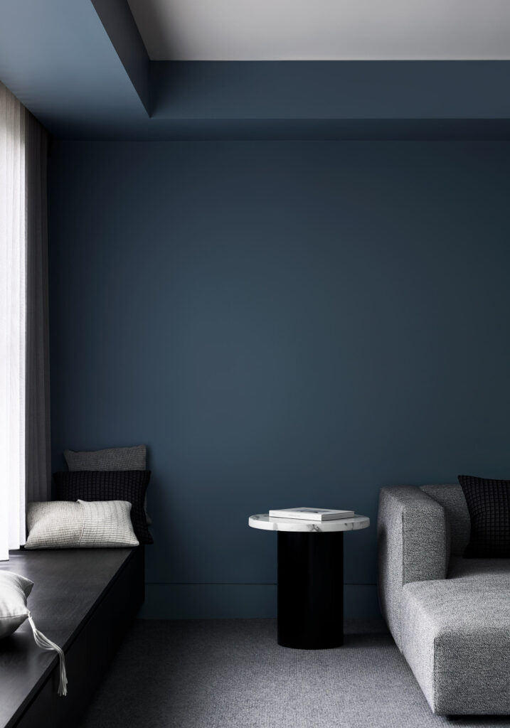 Maike Design lounge room. Bench steat and sheer curtains. Blue painted walls. Marble side table