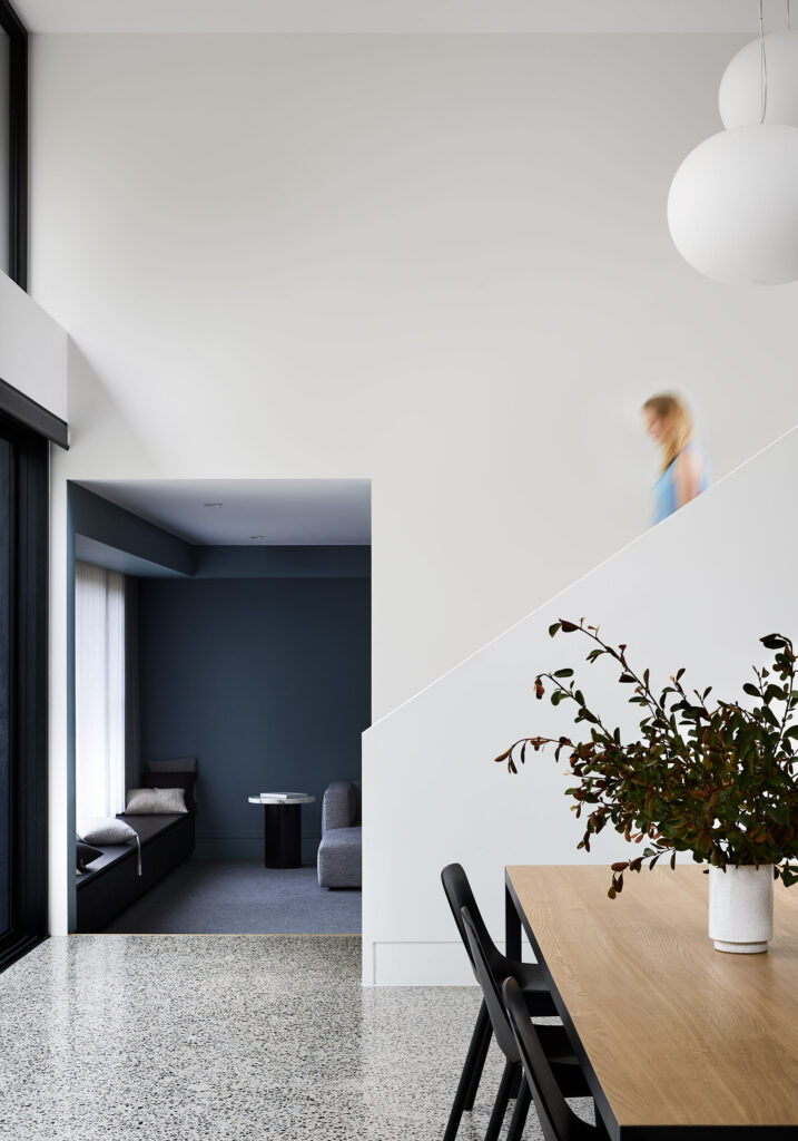Maike Design dining room. Double height space with polished concrete floor. View through to blue painted lounge room